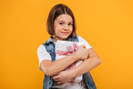 Portrait of a satisfied little schoolgirl hugging gift box over yellow background