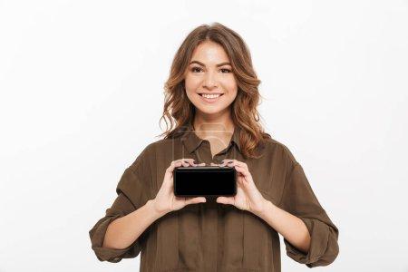 Photo pour Portrait d'une jeune femme confiante montrant un téléphone portable à écran vierge isolé sur fond blanc - image libre de droit