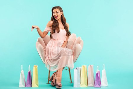 Photo of lovely woman 20s in dress sitting on pink armchair after shopping with lots of colorful bags isolated over blue background
