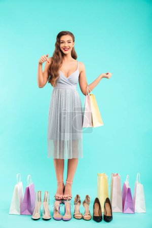 Full length photo of smiling shopper woman 20s in dress posing with different summer shoes and holding shopping bags in hands isolated over blue background