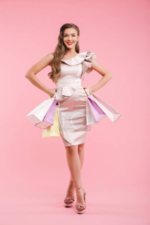 Full length photo of gorgeous woman 20s in dress smiling and holding colorful shopping bags isolated over pink background