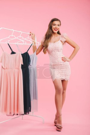 Full length photo of posh young woman 20s smiling and posing with lots of dresses on hangers isolated over pink background