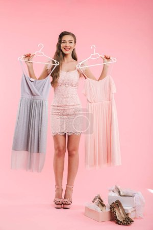Full length photo of joyous young woman 20s holding two dresses on hangers and choosing while shopping isolated over pink background