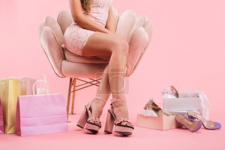 Photo for Cropped photo of young woman in dress with healthy legs crossed sitting in armchair near shopping bags and shoes boxes isolated over pink background - Royalty Free Image