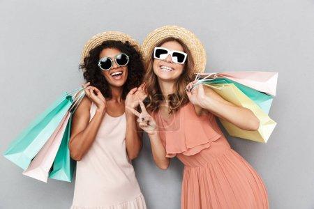 Photo pour Portrait de deux jeunes femmes heureuses vêtues de vêtements d'été tenant des sacs à provisions et montrant un geste de paix isolé sur fond gris - image libre de droit