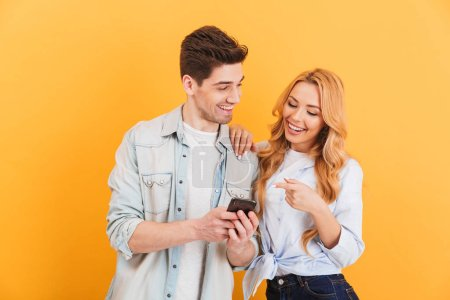 Photo for Photo of happy people man and woman laughing while pointing finger at smartphone isolated over yellow background - Royalty Free Image