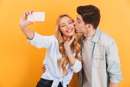 Portrait of lovely couple taking selfie photo on mobile phone while man kissing woman on cheek isolated over yellow background