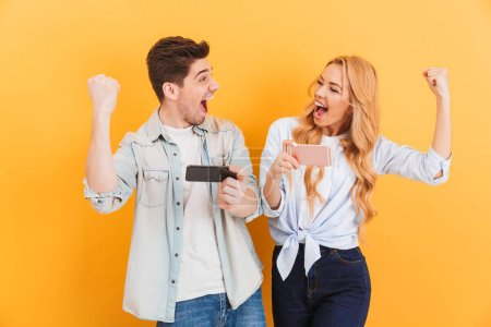 Image of joyous man and woman rejoicing and clenching fists while playing together video games on mobile phones isolated over yellow background