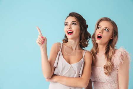 Two beautiful girls 20s wearing party outfit pointing index fingers upward at copyspace with excited faces isolated over blue background