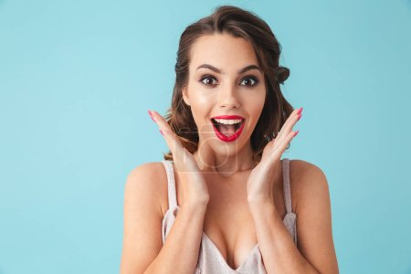 Photo for Surprised happy brunette woman in dress rejoices and looking at the camera over turquoise background - Royalty Free Image