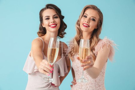 Two happy women in dresses posing together drinking champagne and looking at the camera over turquoise background