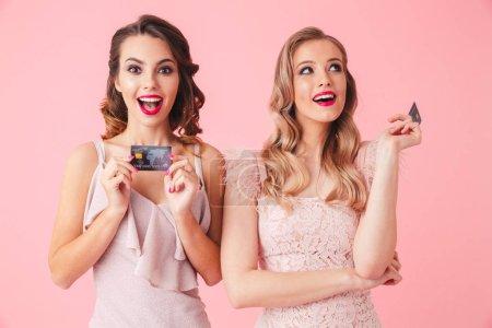 Photo pour Deux femmes intriguées dans des robes posant avec des cartes de crédit et regardant autour sur fond rose - image libre de droit