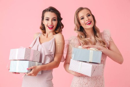 Two cheerful women in dresses holding gift boxes and looking at the camera over pink background