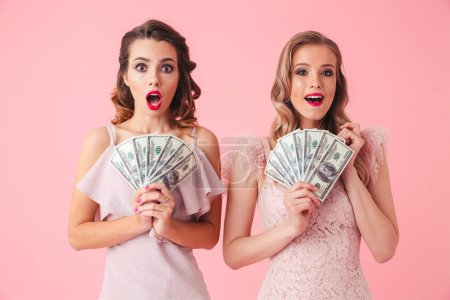 Two excited girls 20s in fancy outfit holding fan of money 100 dollar bills isolated over pink background