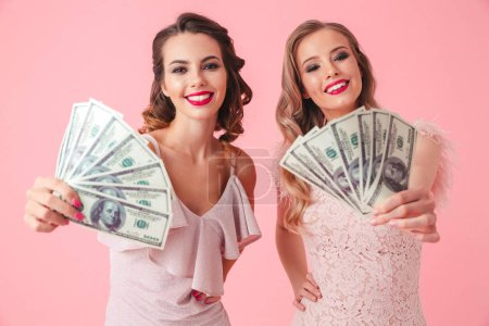 Two young gorgeous women 20s in dresses showing fan of money 100 dollar bills at camera isolated over pink background
