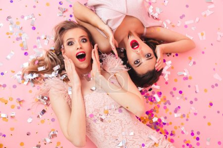 Photo for Image of excited women in dresses lying on the floor under falling colorful confetti at luxury party or carnival isolated over pink background - Royalty Free Image