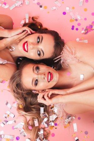 Photo pour Photo verticale de filles brillantes au carnaval souriant et couché sur le sol avec des têtes dans des directions opposées sous des paillettes colorées ou des confettis isolés sur fond rose - image libre de droit