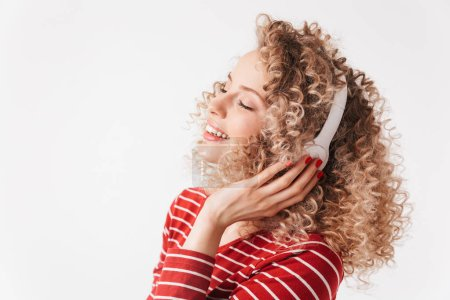 Pleased blonde curly woman in casual clothes and headphones listening music with closed eyes over grey background