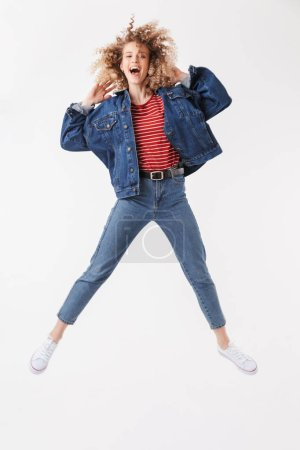 Full length image of Surprised happy blonde curly woman in denim clothes jumping and rejoices while looking at the camera over grey background