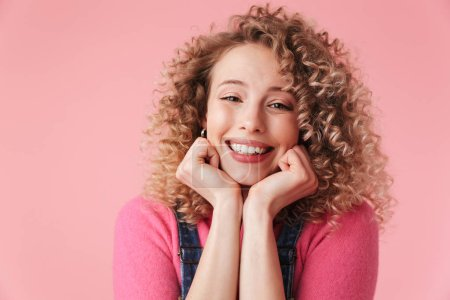 Photo for Close up portrait of smiling young girl with curly hair looking at camera isolated over pink background - Royalty Free Image