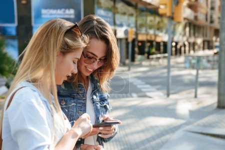Image of two amazing women friends walking outdoors using mobile phone.