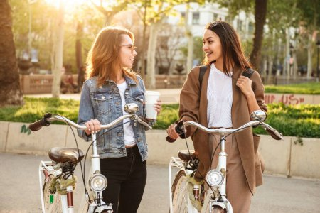 Picture of two young happy women friends outdoors with bicycles in park.