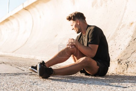 Portrait of an injured sportsman suffering from knee pain while sitting outdoors