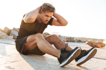 Portrait of a concentrated sportsman doing abs exercises outdoors