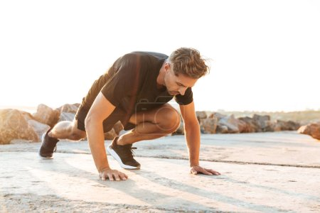 Image of handsome sportsman make sport exercises outdoors at the beach early morning.