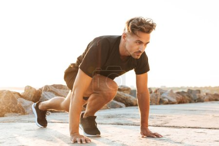 Photo for Image of handsome strong concentrated sportsman make sport exercises outdoors at the beach early morning. - Royalty Free Image