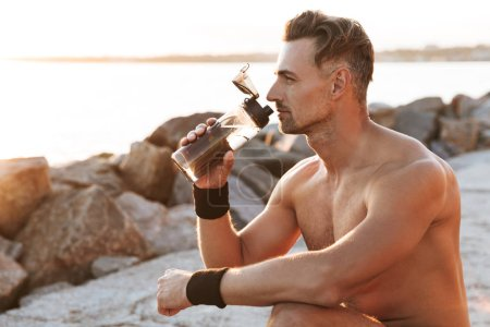 Portrait of a handsome shirtless sportsman resting after jogging and drinking water outdoors