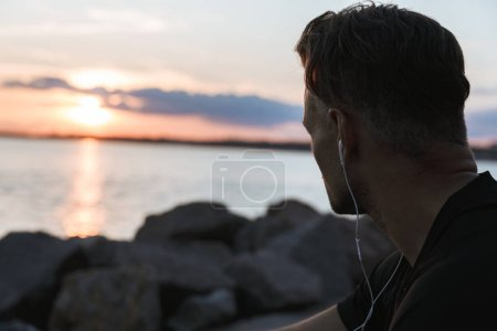 Close up portrait of a handsome sportsman listening to music with earphones while sitting at the beach