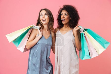 Two excited young girls dressed in summer clothes holding shopping bags and looking away isolated over pink background