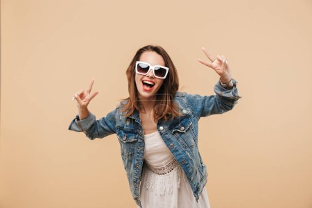 Portrait of a smiling young girl in summer clothes and sunglasses posing while showing peace gesture isolated over beige background