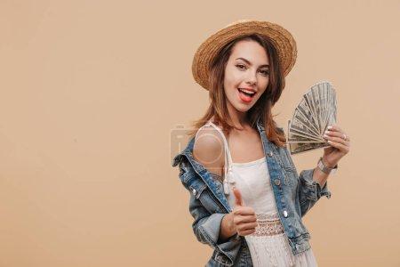 Foto de Retrato de una feliz joven en ropa de verano mostrando billetes de dinero y dando pulgares aisladas sobre fondo beige - Imagen libre de derechos
