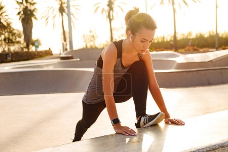 Image of young sports woman make stretching exercises outdoors on the street.