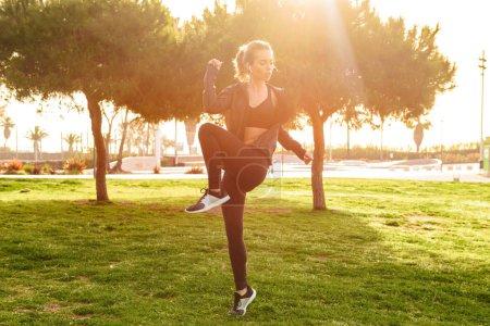 Photo pour Image de magnifique belle jeune femme sportive faire des exercices de sport en plein air . - image libre de droit