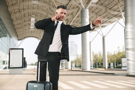 Handsome businessman dressed in suit catching taxi while walking with a suitcas e outside airport terminal and talking on mobile phone