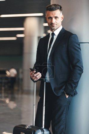Photo pour Homme d'affaires mature souriant tenant un téléphone portable tout en se tenant dans le hall de l'aéroport avec une valise - image libre de droit