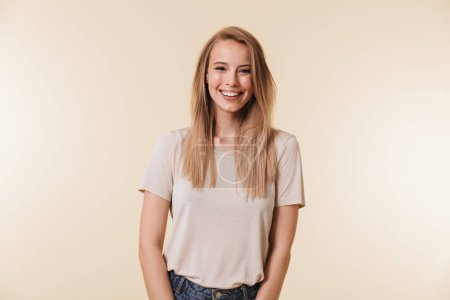 Image of beautiful pleased woman 20s wearing casual t-shirt laughing and looking at you with happy smile isolated over beige background in studio