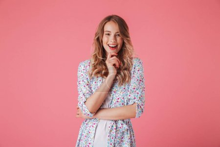 Photo for Portrait of a smiling young woman in summer dress looking at camera isolated over pink background - Royalty Free Image
