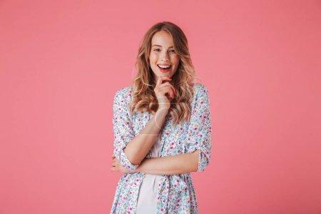 Photo pour Portrait d'une jeune femme souriante en robe d'été regardant la caméra isolée sur fond rose - image libre de droit