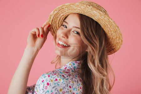 Close up portrait of a pretty young woman in summer dress and straw hat posing and looking at camera isolated over pink background