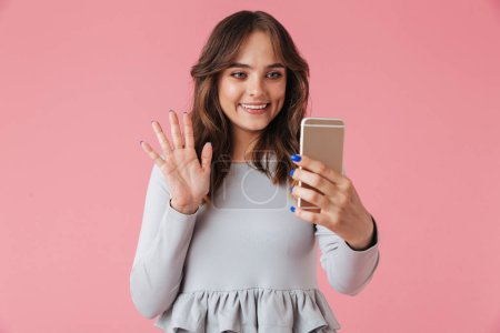 Photo of cute young pretty woman standing isolated over pink wall background looking aside talking by mobile phone.