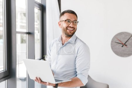 Image of joyful business man wearing white shirt looking aside at copyspace while holding silver laptop during work in office interior