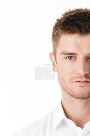 Foto de Imagen recortada de la cara de un hombre joven serio mirando a cámara aislada sobre fondo blanco - Imagen libre de derechos