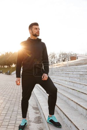 Photo pour Portrait de grave jeune sportif dans les écouteurs, faire des exercices sur les étapes à l'extérieur - image libre de droit