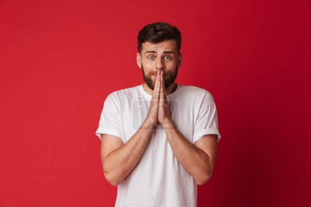 Photo for Picture of hopeful young man standing isolated over red wall background make hope please gesture. - Royalty Free Image