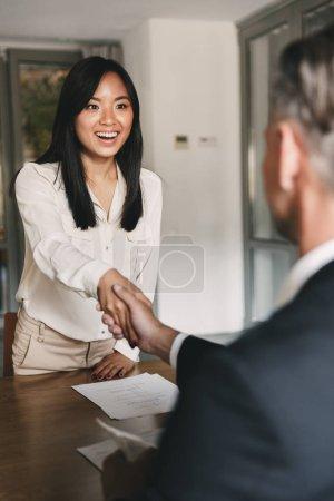Photo pour Concept de Business, de carrière et de placement - handshaking heureuse femme asiatique avec directeur tête mâle ou l'employeur de grande entreprise après des négociations fructueuses ou entrevue - image libre de droit