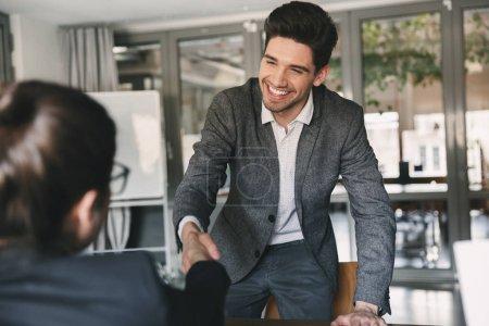 Photo pour Concept d'affaires, de carrière et de placement - joyeuse jeune homme souriant et serrant la main de femme d'affaires lorsqu'a été recruté au cours de l'entrevue au bureau de 30 ans - image libre de droit
